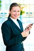 Young happy business woman with a mobile phone in hand Stock Photos