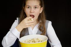 surprised girl with popcorn on a black background - stock photo