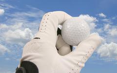 Golf glove,ball and sky Stock Photos