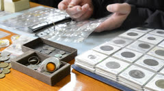 Numismatist looks old coins in albums - stock footage