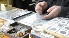 Numismatist looks old coins in albums Stock Footage