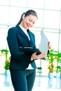 Young happy business woman with an open folder in hand - stock photo