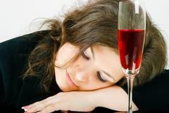 Sleeping girl and a glass of wine Stock Photos