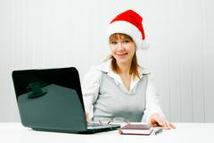 Girl in a christmas hat with a laptop Stock Photos