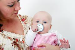 baby with a pacifier in the arms of mother - stock photo