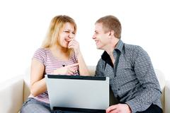 Stock Photo of young couple with a laptop on the background of isolation