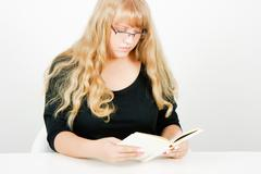 blonde girl with glasses reading - stock photo