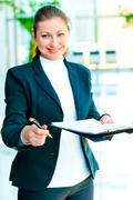 Smiling business woman offers to sign the document - stock photo