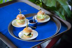 Delicious mini burger canapes on a white plate Stock Photos