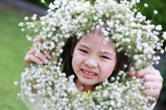 cute little girl showing a flower tiara - stock photo