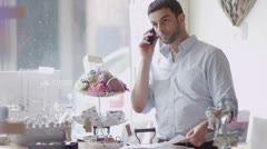 Attractive male business owner on the phone from behind the counter of his shop Stock Footage
