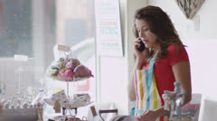 Attractive female business owner on the phone behind the counter of her shop Stock Footage