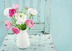 Stock Photo of white and pink flowers on light blue chair