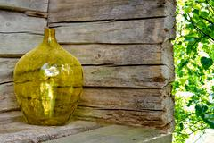 Yellow glass vase on a wooden house exterior Stock Photos