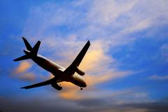 Commercial aircraft landing from bright twilight sunset sky Stock Photos