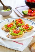 Crostini with avocado and tomato - stock photo