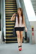 Young business woman walking in front of escalator Stock Photos
