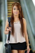 young business woman walking in front of escalator - stock photo