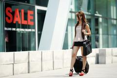 young business woman walking outside of shopping plaza with her rolling lugga - stock photo