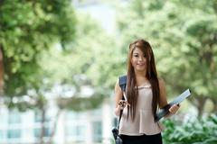 Young woman in business attire, carrying briefcase and holding folder standin Stock Photos