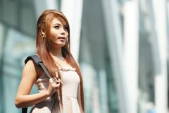 Beautiful business woman walking outside her office with briefcase. Stock Photos