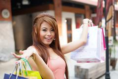 beautiful young woman shows an ecstatic expression while holding shopping bag - stock photo