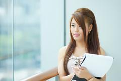 portrait of young business woman standing near window in modern office and wr - stock photo