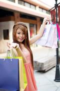 Beautiful young woman shows an ecstatic expression while holding shopping bag Stock Photos