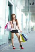 Stock Photo of beautiful young woman shows an ecstatic expression while holding shopping bag