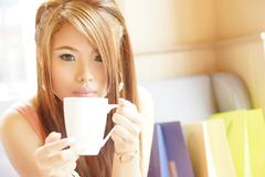 Stock Photo of closeup beautiful woman sitting in cafe holding and drinking coffee.