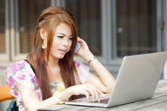 young attractive business woman working on her laptop at outdoors cafe, she l - stock photo