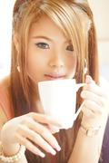 Closeup beautiful woman sitting in cafe holding and drinking coffee. Stock Photos