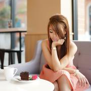 young beautiful woman sitting in cafe and looking at her rose. she very bored - stock photo