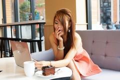young business woman sitting in cafe with her laptop. she look very yawning. - stock photo