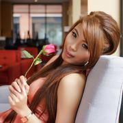 portrait of young beautiful woman holding a red rose at the cafe. - stock photo