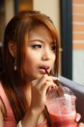 young beautiful woman sitting in cafe holding and drinking a fruit smoothie t - stock photo