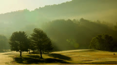 Time lapse fog lift mountain golf course Stock Footage