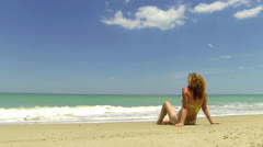 Woman relaxing sitting on a Florida beach Stock Footage