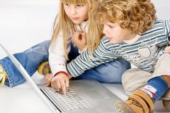 children turning on computer - stock photo