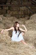 woman in white dress on haystack - stock photo
