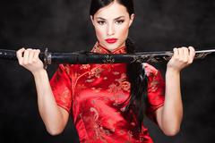Woman holding katana weapon Stock Photos