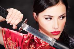woman holding katana weapon - stock photo