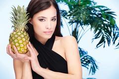 woman holding pineapple - stock photo
