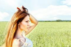 Woman at wheat field on sunny day Stock Photos