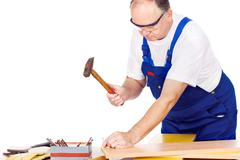 worker knocking the nail in board - stock photo