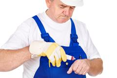 Worker putting cream on his wound Stock Photos