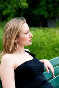 Woman sitting on the bench in park Stock Photos