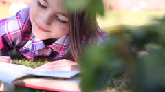 Little girl reading a book in summer on grass.Girl Reading Stock Footage