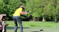Young golfer tees off side view Stock Footage