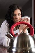 Young woman standing in kitchen holding a coffee cup Stock Photos